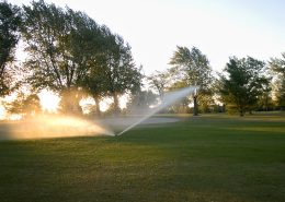 Watering the golf course very early in the morning.